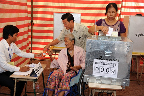 A Cambodian woman (R) casts her vote at a polling station in Phnom Penh on June 3, 2012.  Cambodians on June 3 cast their votes for commune council candidates during local elections.    AFP PHOTO / TANG CHHIN SOTHY